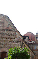 Firenze: A partial view of the ancient church of San Lorenzo, with a part of the façade, the bell tower and the main dome, where are located the Medici chapels. The typical ancient colors of the walls and of the roof are enhanced by the top of a green tree. This photo is an enlargement of a part of the original image.