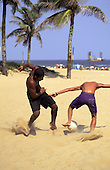 Rio de Janeiro, Brazil. Two boys playing football on the beach.