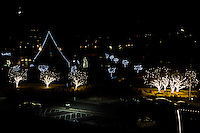 A single parking lot light shines while multiple trees draped in holiday lights glow under a waxing crescent moon.