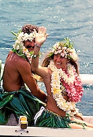 A wedding couple dressed in Polynesian-style  attire wave from a canoe in Kapoho on the Big Island of Hawaii.
