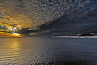 Fine Art Landscape Photograph of a dramatic sunset over the Atlantic Ocean and the port of Ponta Delgada in the Azores.