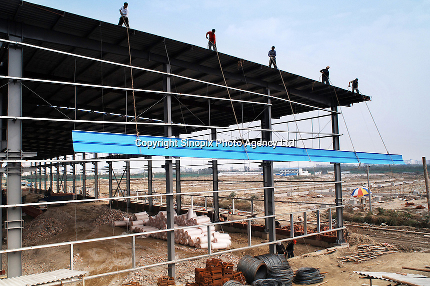 Workers work in construction site of a new factory for digital television in Chengdu, China..31 OCT 05