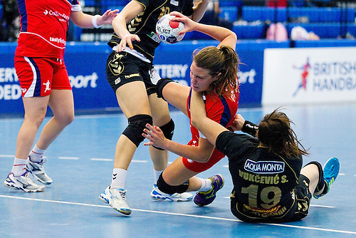 30 MAY 2012 - LONDON, GBR - Ewa Palies (GBR) of Great Britain (second from right, in red and blue) finds her path to goal blocked by Sara Vukcevic (MNE) of Montenegro (right, in black and gold) during the women's 2012 European Handball Championship qualification match at the National Sports Centre in Crystal Palace, Great Britain .(PHOTO (C) 2012 NIGEL FARROW)