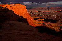 Sandstone-capped escarpment of the Vermilion Cliffs tumbles 3,000 feet to the Grand Canyon in northern Arizona. Vast scale makes the Colorado River's down-cutting appear as a series of narrow, winding incisions near Marble Canyon.  The remote 293,000 acre monument features a majestic grand terrace rising at the edge of the Paria Plateau.