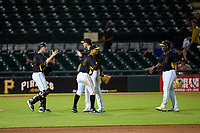 Bradenton Marauders catcher Eli Wilson (12), pitcher Santiago Florez (50), first baseman Endy Rodriguez (5), and third baseman Alexander Mojica (28) celebrate after the final out of a game against the Daytona Tortugas on June 9, 2021 at LECOM Park in Bradenton, Florida.  (Mike Janes/Four Seam Images)