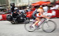 17 JUL 2011 - HAMBURG, GER - A television cameraman films a competitor as she cycles through Hamburg during the women's round of triathlon's ITU World Championship Series .(PHOTO (C) NIGEL FARROW)