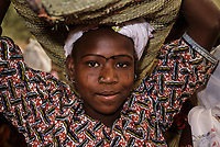 Young Nigerien Woman with Facial Scarification and Nose Pin, Carrying Basket on Head, Baleyara, Niger.