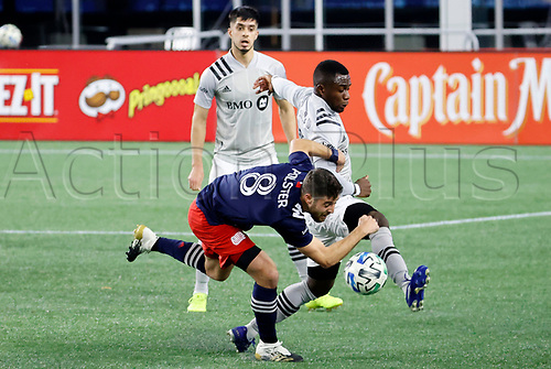 20th November 2020; Foxborough, MA, USA;  Montreal Impact defender Zachary Brault-Guillard plays the ball through New England Revolution defender / midfielder Matt Polster (8) during the MLS Cup Play-In game between the New England Revolution and the Montreal Impact