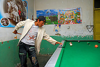 Tibetan teenager plays billiards at one of the several halls in the Barkhor area of Lhasa, Tibet.