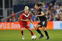 USWNT midfielder Lauren Cheney (12) facing up against Canada forward Kelly Parker.