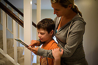 Jack Ursitti, age 7, looks at his schedule for the day's activities with Sarah Hoey, of the Nashoba Learning Group, in his home in Dover, Mass., on Monday, July 25, 2011.  Jack has been diagnosed with autism.  After school at his home, Jack works with his teacher and a therapist to do educational and independent leisure activities...Jack Ursitti wears a small GPS ankle bracelet at all times in case he runs off from his family or caretakers. The device will be activated if he goes missing, allowing police and other searchers to find him.