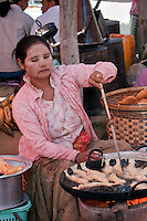 Myanmar, Burma.  Burmese Woman Cooking Snacks in the Five-day Market, Inle Lake, Shan State.  She is wearing thanaka paste on her face, a cosmetic sunscreen.