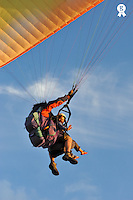 Girl flying in tandem, waving from paraglider (Licence this image exclusively with Getty: http://www.gettyimages.com/detail/92351865 )