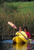 Couple paddling a kayak on a lake.