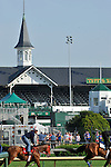 Kentucky Derby Mini-Marathon runners run through the Churchill Downs infield while Derby contending horses work on Saturday, April 30, 2011.