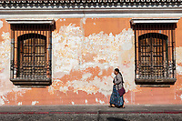 Antigua, Guatemala.  Woman Walking Past an Old House with Flaking Paint.
