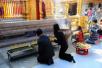 People burning incense sticks and candles to pay in front of a altar with golden Buddha statues in Wat Phrathat Doi Suthep temple, Thailand, Southeast Asia. Wat Phrathat Doi Suthep is a Buddhist temple in Chiang Mai Province, Thailand, The temple is often referred to as 'Doi Suthep' although this is actually the name of the mountain it is located on.