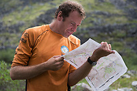 Man reads a topo map in the Gates of the Arctic National Park, Alaska