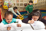 Education Preschool Headstart 3-4 year olds two girls drawing on pads with markers has boys play with trucks behind them