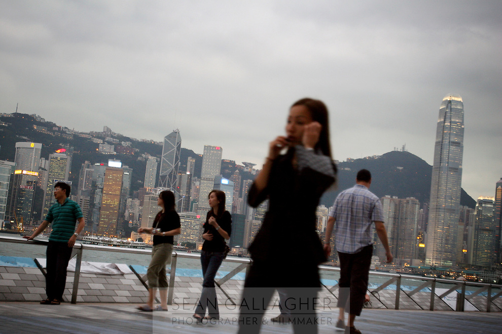 CHINA. Hong Kong. Hong Kong residents and tourists walk past the famous Hong Kong skyline. Officially the Hong Kong Special Administrative Region, it is a territory located on China's south coast on the Pearl River Delta. It has a population of 6.9 million people, and is one of the most densely populated areas in the world. 2008