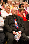 © Joel Goodman - 07973 332324 . 24/04/2014 . Manchester , UK . A man wearing a Union Jack tie and carrying a picture of Nigel Farage in the audience at a UKIP conference rally at the Free Trade Hall in Manchester . Photo credit : Joel Goodman