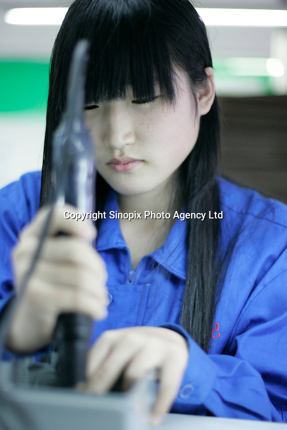 Girls assemble boxes for breaker switches at a factory in Dongguan, China. The products are destined for the US housing market.