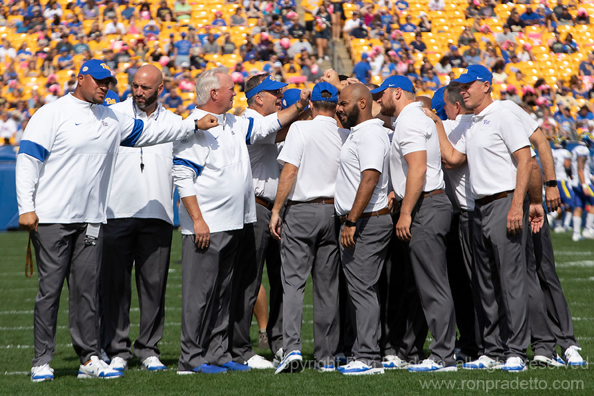 The Pitt football coaches led by Pat Narduzzi (middle) huddle before the game. The Pitt Panthers defeated the Delaware Blue Hens 17-14 in a football game at Heinz Field in Pittsburgh, Pennsylvania on September 28, 2019.