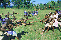 Uganda. Kayunga district. Kangulumira. School. A group of pupils play in the grass during the gymnastic lesson. The game will decide which group is the strongest to pull a rope and push its opponents on the ground.  © 2004 Didier Ruef