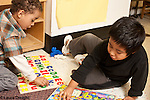Education preschool 3 year olds two boys working on puzzles on floor separately