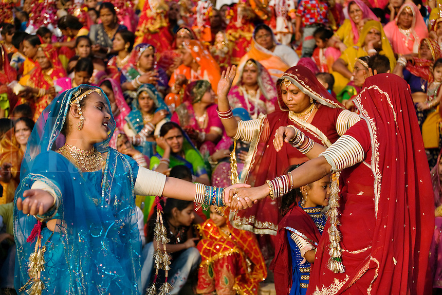 Rajasthani women dressed in thier finest dance at the GANGUR FESTIVAL also known as the MEWAR FESTIVAL - UDAIPUR, RAJASTHAN, INDIA