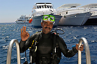 Smiling man scuba diver climbing the ladder of a diving boat off the coast of Safaga and doing the OK sign, Egypt, Red Sea (MR)