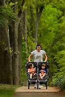 A woman pushes her two children in a stroller down Queens Road West in the Myers Park neighborhood in Charlotte, NC. Myers Park is one of the premier neighborhoods in North America and known for its large canopy of trees.