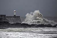 Pictured: Waves crash against the promenade wall by the lighthouse in Porthcawl, south Wales, UK. Tuesday 18 December 2018<br /> Re: Heavy rain has been forecast for much of the day in areas of south, west and parts of mid Wales with the Met Office having issued a yellow warning.<br /> Wind gusts along the coast are expected to reach up to 65 mph, while in inland areas they could reach 50 mph.