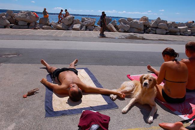 family sunbathing with their dog. Piran , Slovenia