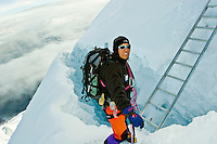 Mountain climber crossing a crevasse near the summit of Mount Cotopaxi, a 5,897 meter ( 19,348 feet ) high active volcano near Quito, Ecuador.  Model Released