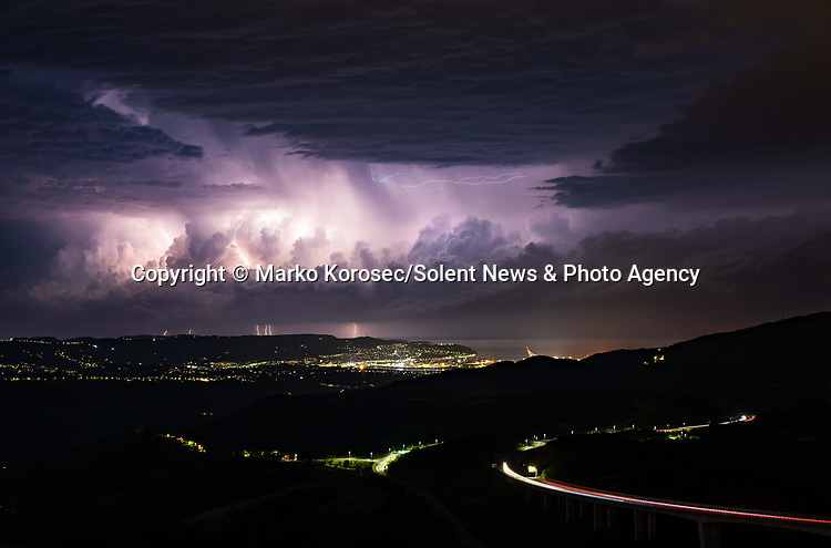 Pictured:  A storm in Crni Kal, Slovenia<br /> <br /> Lightning from a huge supercell storm strikes the ocean and illuminates the sky as boats float on the calm water.  In another image enormous clouds gather over a city as they crackle with forks of electric light.<br /> <br /> The supercells can last for up to ten hours and can cause devastating tornadoes and torrential hailstone-filled thunderstorms.  The stunning images were taken in Padova and Trieste in Italy and in Ljubljana, Dloneja vas and Crni Kal in Slovenia by weather information supervisor and amateur photographer Marko Korosec.  SEE OUR COPY FOR DETAILS.<br /> <br /> Please byline: Marko Korosec/Solent News<br /> <br /> © Marko Korosec/Solent News & Photo Agency<br /> UK +44 (0) 2380 458800