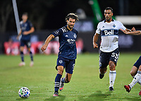 LAKE BUENA VISTA, FL - JULY 26: Graham Zusi of Sporting KC passes the ball away from Ali Adnan of Vancouver Whitecaps FC during a game between Vancouver Whitecaps and Sporting Kansas City at ESPN Wide World of Sports on July 26, 2020 in Lake Buena Vista, Florida.