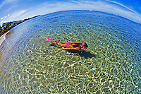 Fisheye view of  female snorkeler at Lahaina, Maui wearing a pink swimsuit.