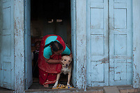 A woman plays with her dog in her house in Bhaktapur, near Kathmandu, Nepal. May 04, 2015