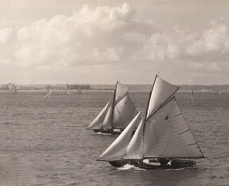 The Dublin Bay 21s Estelle and Maureen in their jackyard-topsail-rigged heyday on a Saturday afternoon in the 1950s. The background speaks volumes of the low level of national economic activity at the time. Over towards the inner bay at Poolbeg, the most conspicuous building seems to be the former Pigeon House Hotel, which dated back to the 1740s. Power stations and major port development were still in the future, and ship movements were minimal