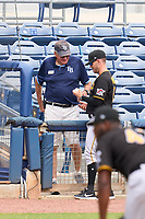 A stadium usher gives the first home run ball of FCL Pirates Black Henry Davis (not shown) to coach Casey Harms (19) after retrieving it during a game against the FCL Rays on August 3, 2021 at Charlotte Sports Park in Port Charlotte, Florida.  Davis was making his professional debut after being selected first overall in the MLB Draft out of Louisville by the Pittsburgh Pirates.  (Mike Janes/Four Seam Images)