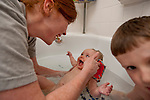Sarah and Marianne make each other smile during bath time while Benjamin finds his own entertainment.