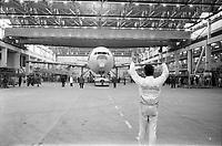 Usine de l'Aérospatiale de Saint-Martin-du-Touch, grand hall de montage. 5 février 1972. Vue d'ensemble de face de l'Airbus A300 B tracté par un tracma ; au 1er plan technicien de dos guide l'avion, bras levés. Cliché pris lors du 1er déplacement tracté de l'avion encore en cours de montage.