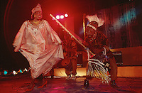 Mali. Bamako. The musician Oumou Sangare sings and dances while one of her musicians plays the traditionnal kora during a concert at Mamadou Konate stadium. © 1997 Didier Ruef