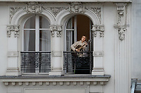 ragazza alla finestra a Parigi suona la chitarra durante il ringraziamento ai medici e infermieri girl playing guitar from a window, in Paris
