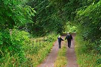 Country road. Two people, an adult and a child, walking. Through the forest. Smaland region. Sweden, Europe.
