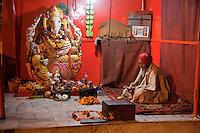 India, Rishikesh.  Hindu Priest Sitting in a Shrine to Ganesh.