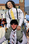 Man dressed like Moe of the Three Stooges with a figure of Larry on his shoulders at the Doo Dah Parade in Pasadena, CA