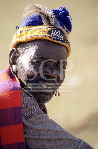 "Lolgorian, Kenya. Siria Maasai Manyatta; elder wearing a blue and yellow woolen hat with ""Holy"" badge, beard."