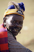 "Lolgorian, Kenya. Siria Maasai Manyatta; elder wearing a blue and yellow woolen hat with ""Holy"" badge, beard."